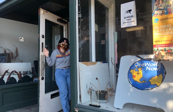 A photo of alum and summer intern Chelsea Morales standing at the door of the OneWorld Now office, welcoming people inside.